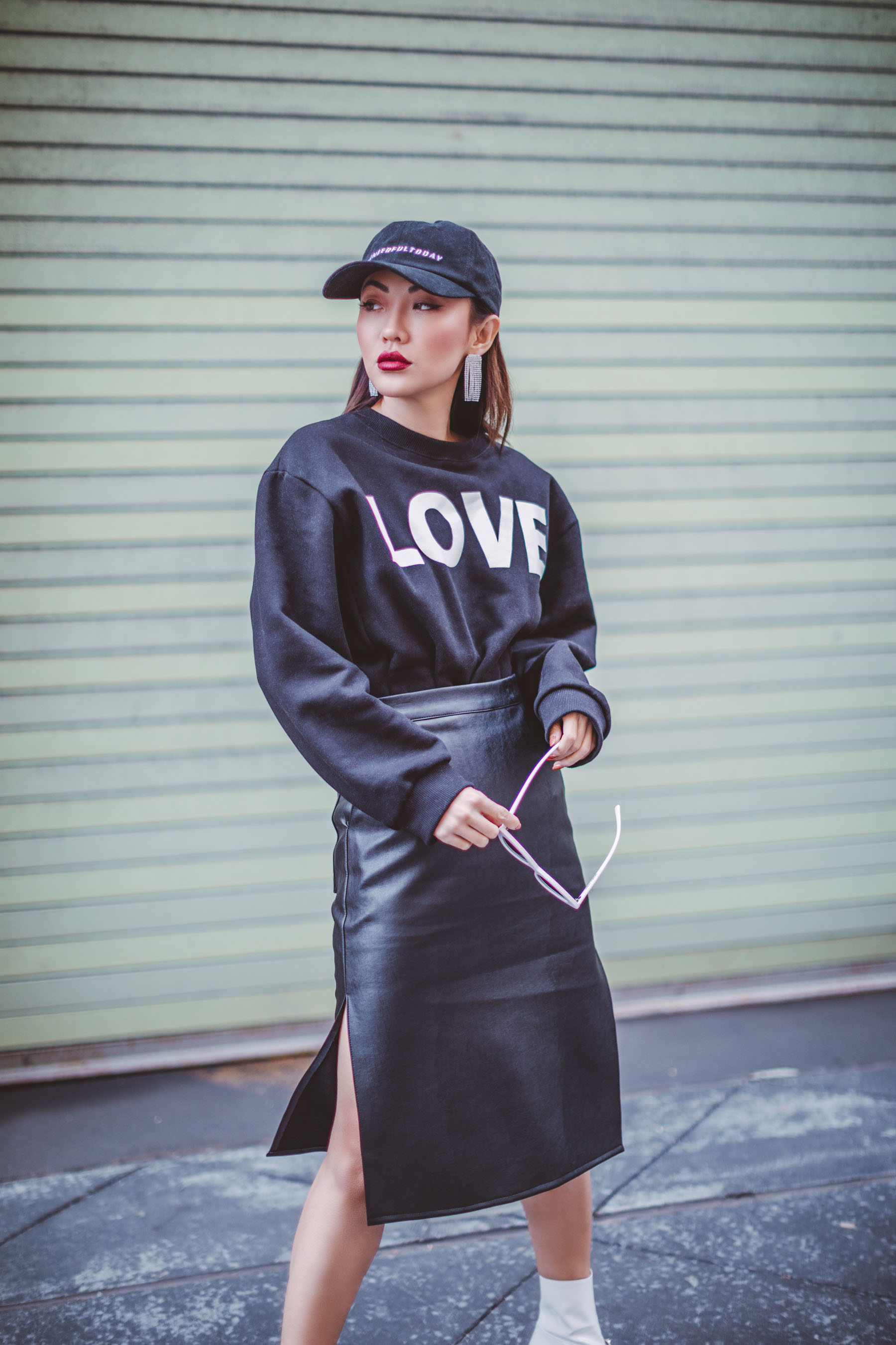 How to Look Stylish in a Quilted Puffer Jacket // Notjessfashion.com // oversized graphic sweater with baseball cap, leather skirt, and pink sunglasses, new york fashion blogger, asian blogger