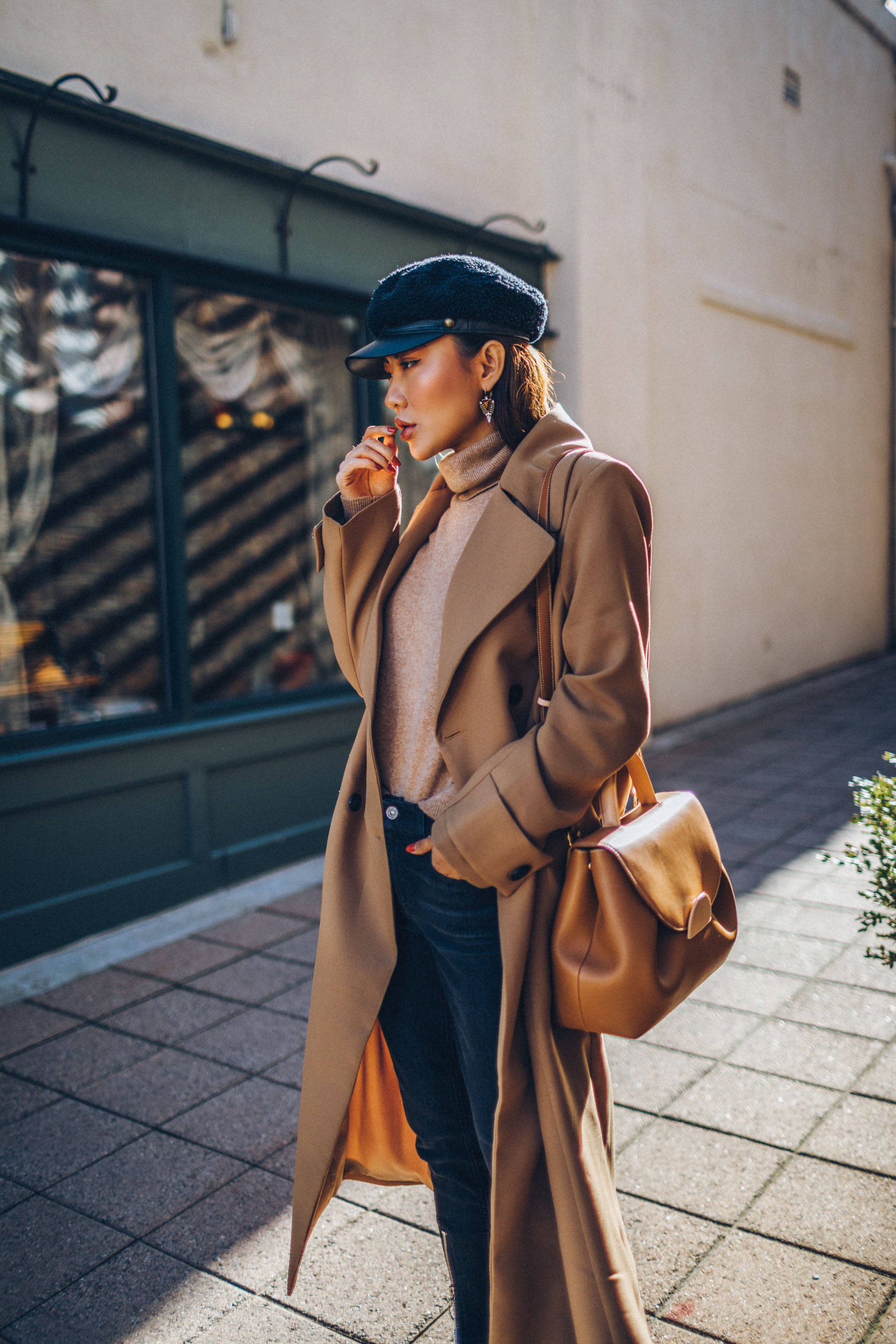 How to Buy an Investment Coat - Belted Camel Coat with Dark Denim Baker Boy Cap and Satchel // Notjessfashion.com // New York fashion blogger, asian blogger, classic camel coat, winter outfit, classic winter outfit, cozy layered outfut, nude boots, nude bag, baker boy hat, how to style camel coat, jessica wang, fashion blogger, street style, fashion blogger street style, oversized coat, duster coat, maxi coat
