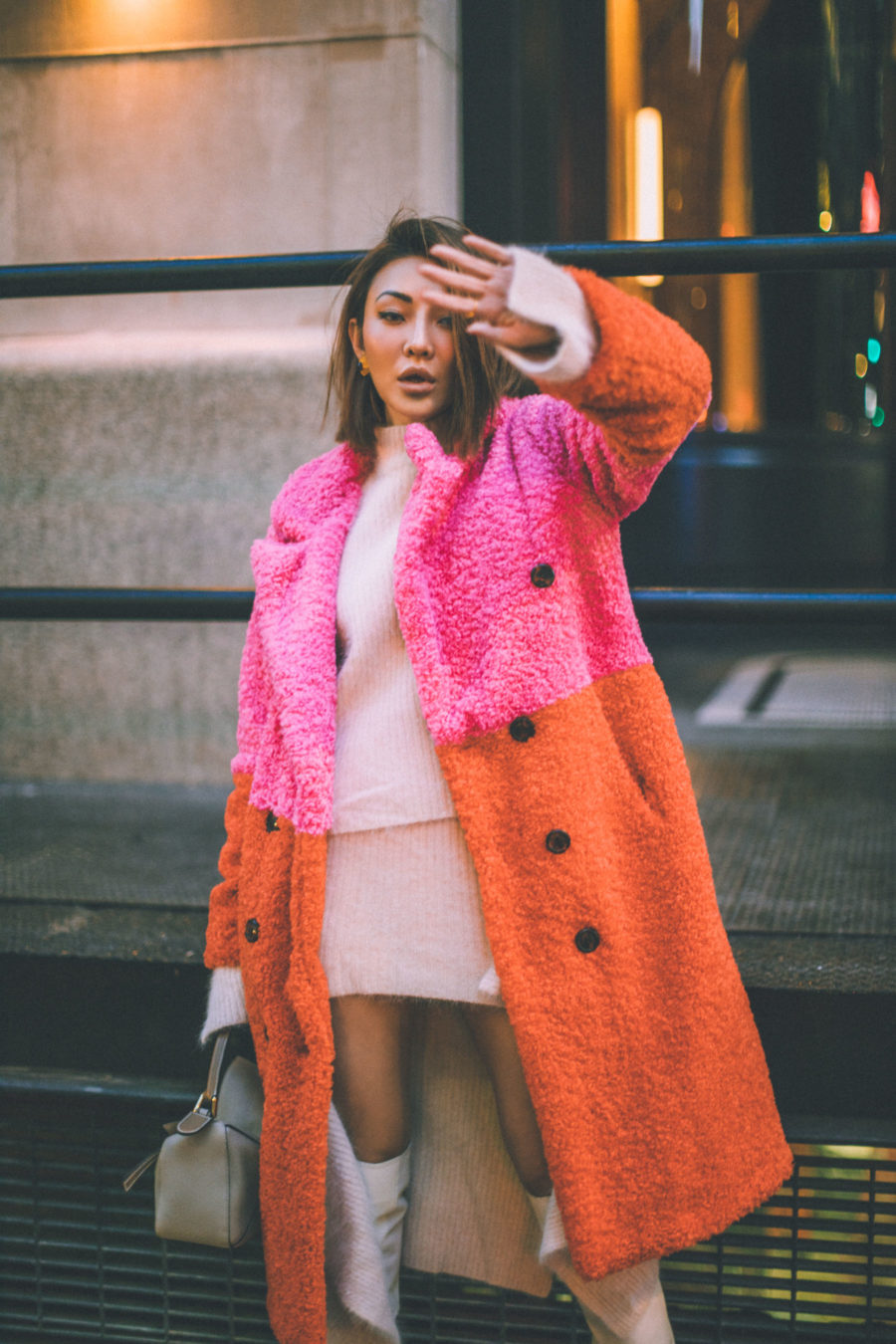 fashion blogger jessica wang wears festive winter outfit with a colorblock coat and white boots // Notjessfashion.com