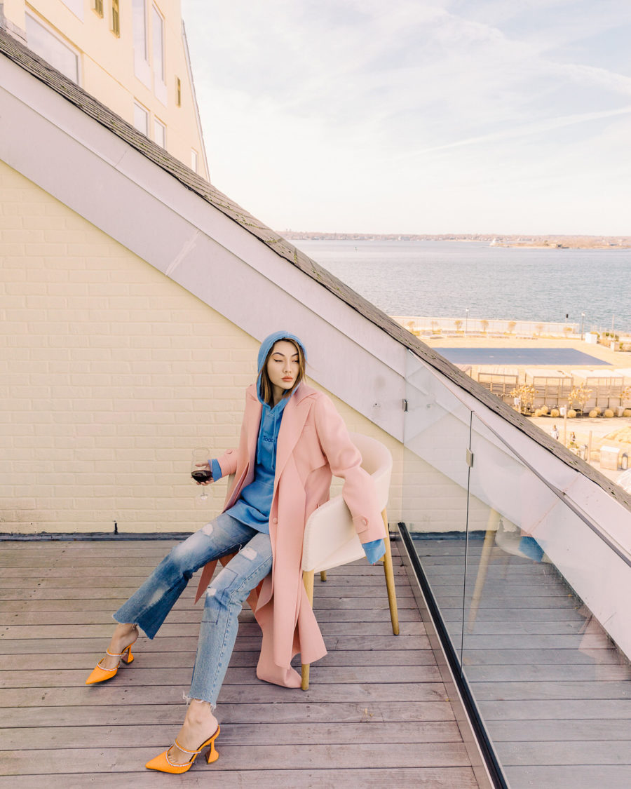 fashion blogger jessica wang shares ways to look more sophisticated on a budget wearing a pink trench coat blue hoodie and amina muaddi heels // Notjessfashion.com